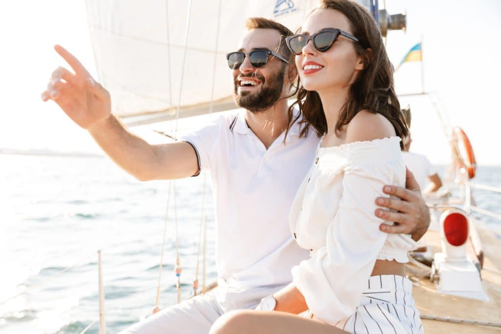 Image of a happy optimistic cheery young loving couple outdoors on yacht in sea pointing aside hugging.