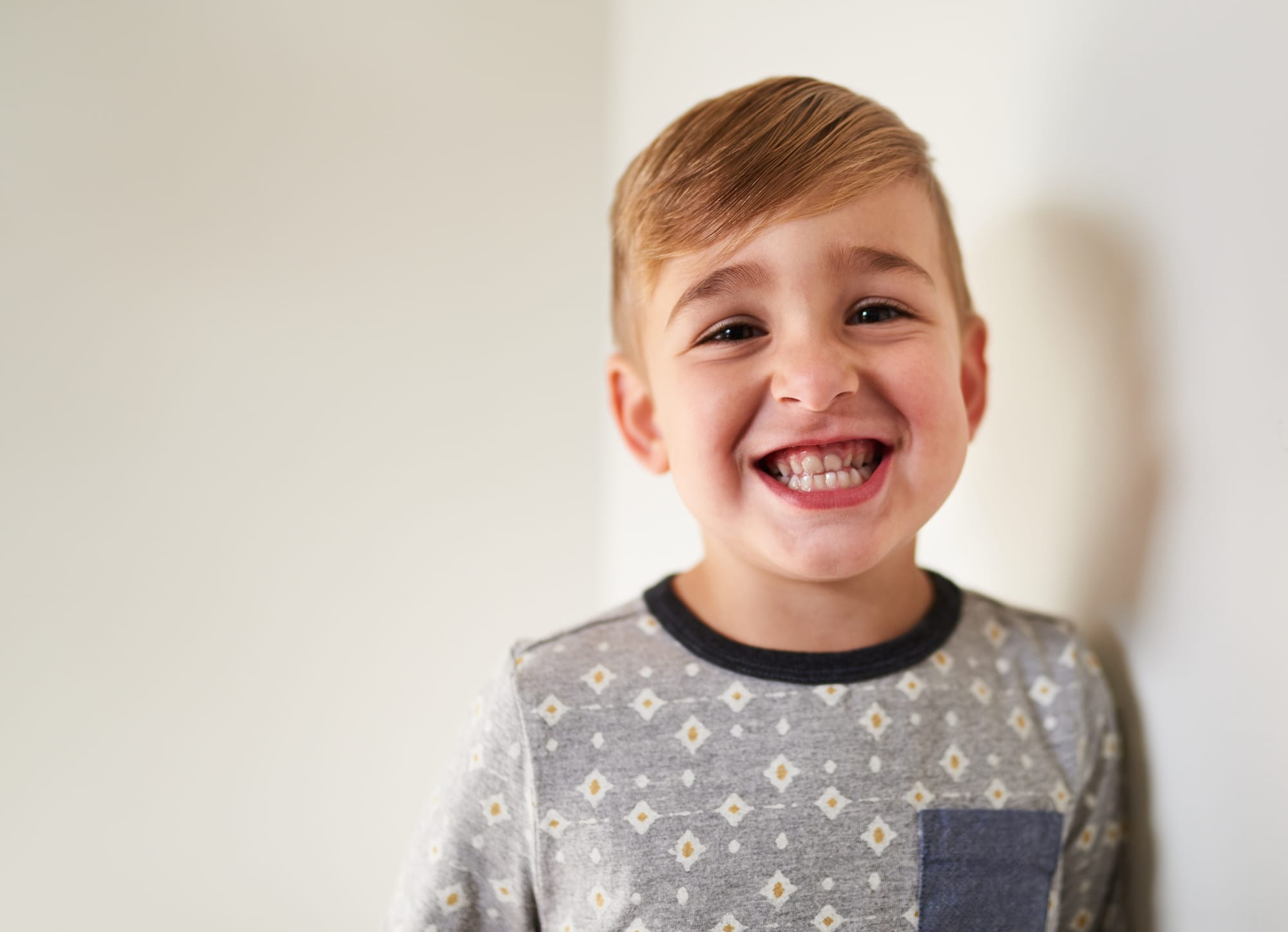 Isolated closeup shot of funny, cheerful little kid boy face looking at camera with adorable smile showing teeth, wearing hipster shirt with white background