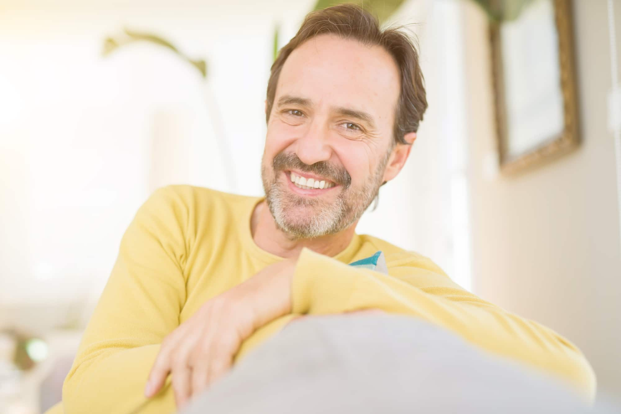 Handsome middle age man sitting on the sofa relaxed and smiling at the camera at home