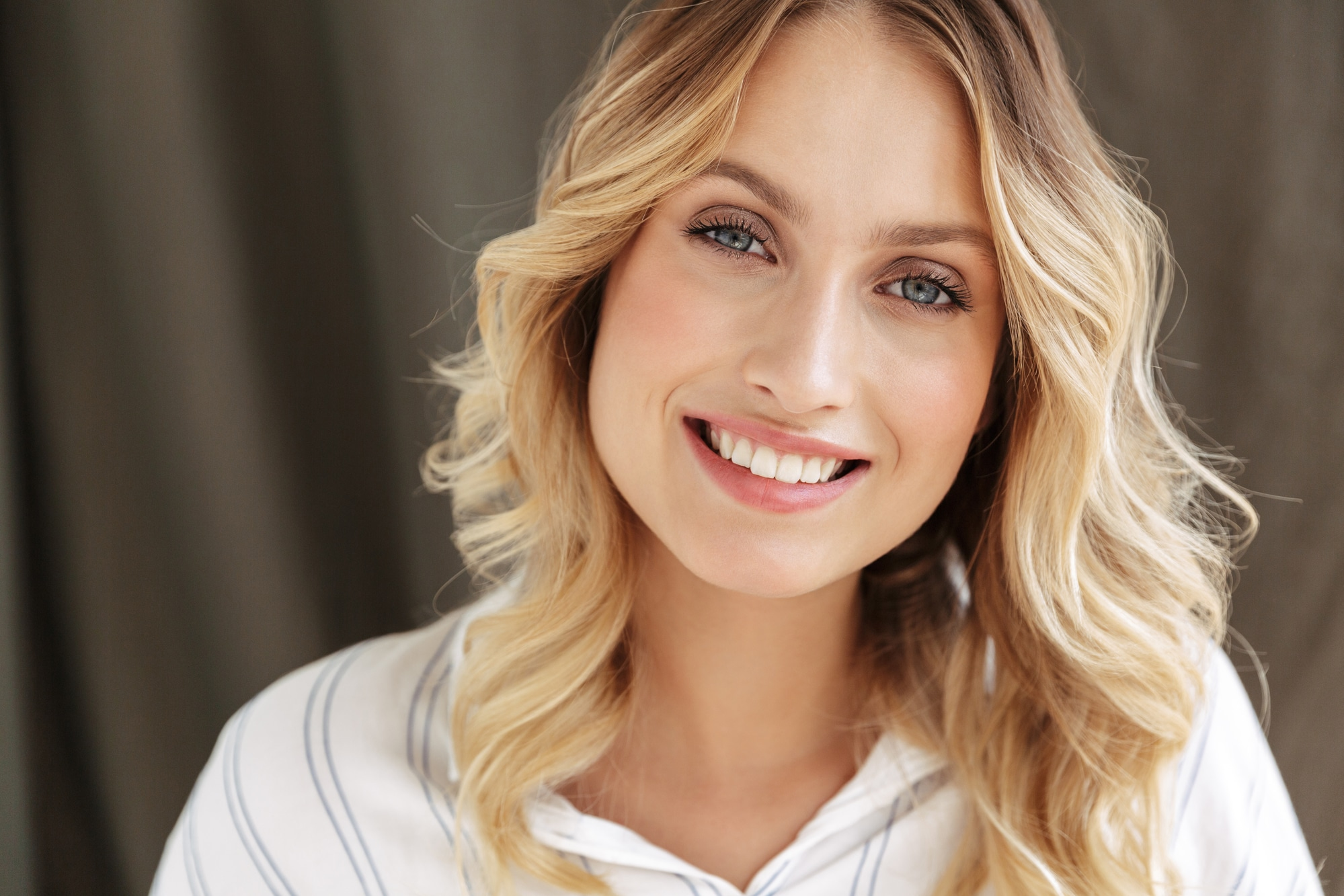 Close up of a beautiful smiling blonde woman wearing shirt looking at camera over gray wall