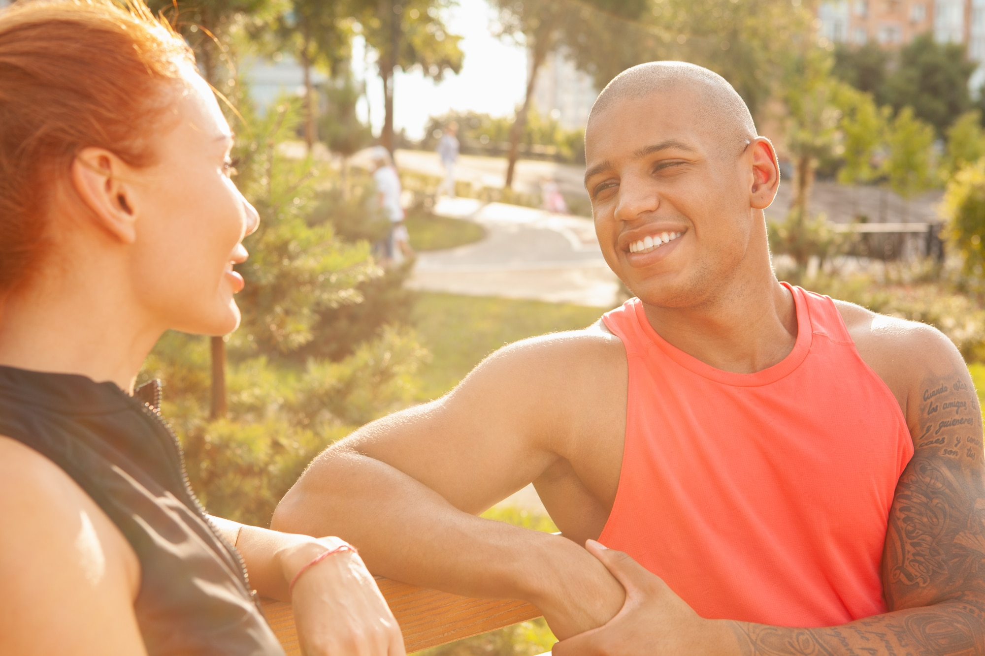 Happy handsome African man laughing, talking to his girlfriend while resting outdoors on a warm sunny day. Beautiful couple resting on the bench after exercising together