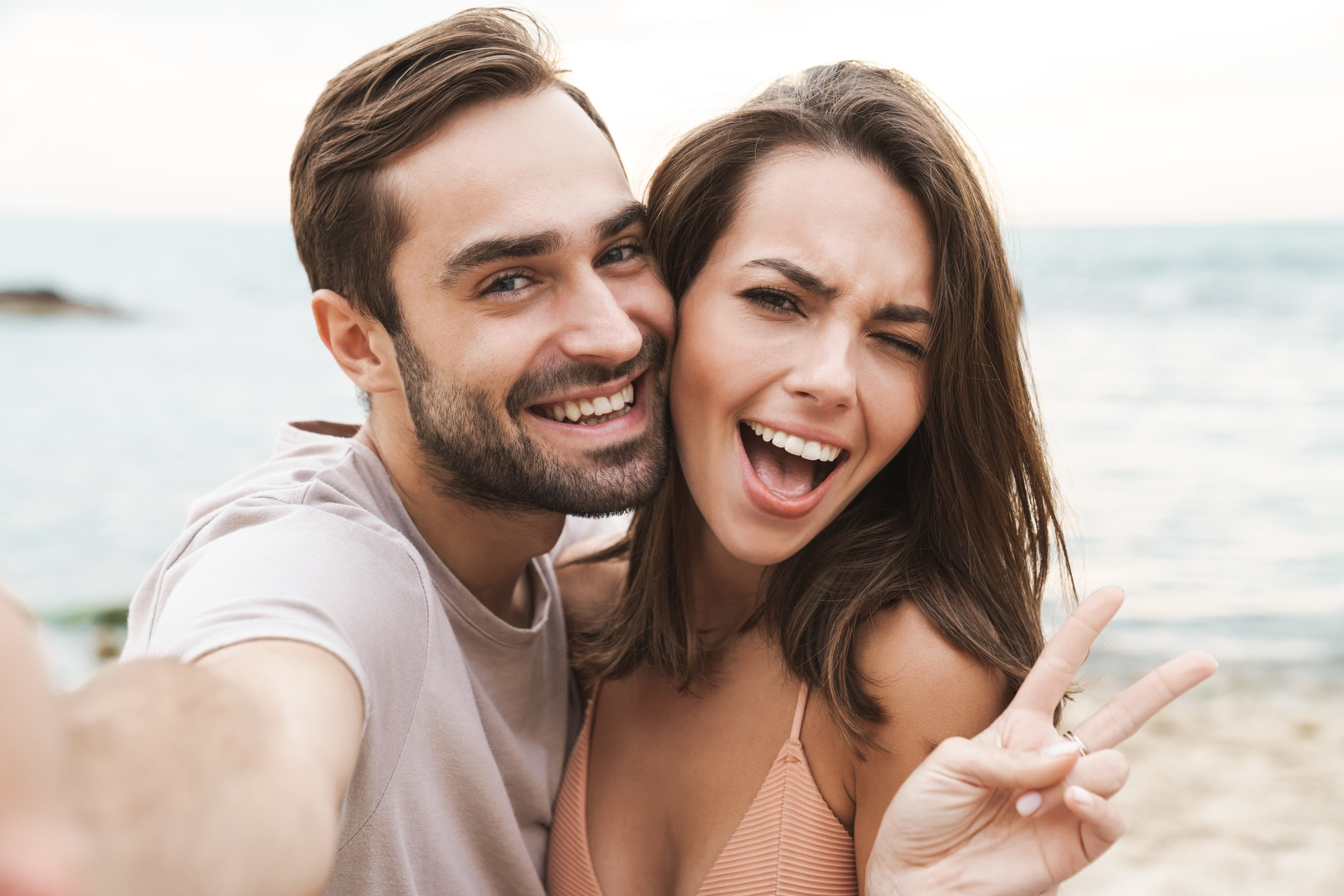 Photo of smiling young couple gesturing peace sign and taking selfie photo while resting on sunny beach