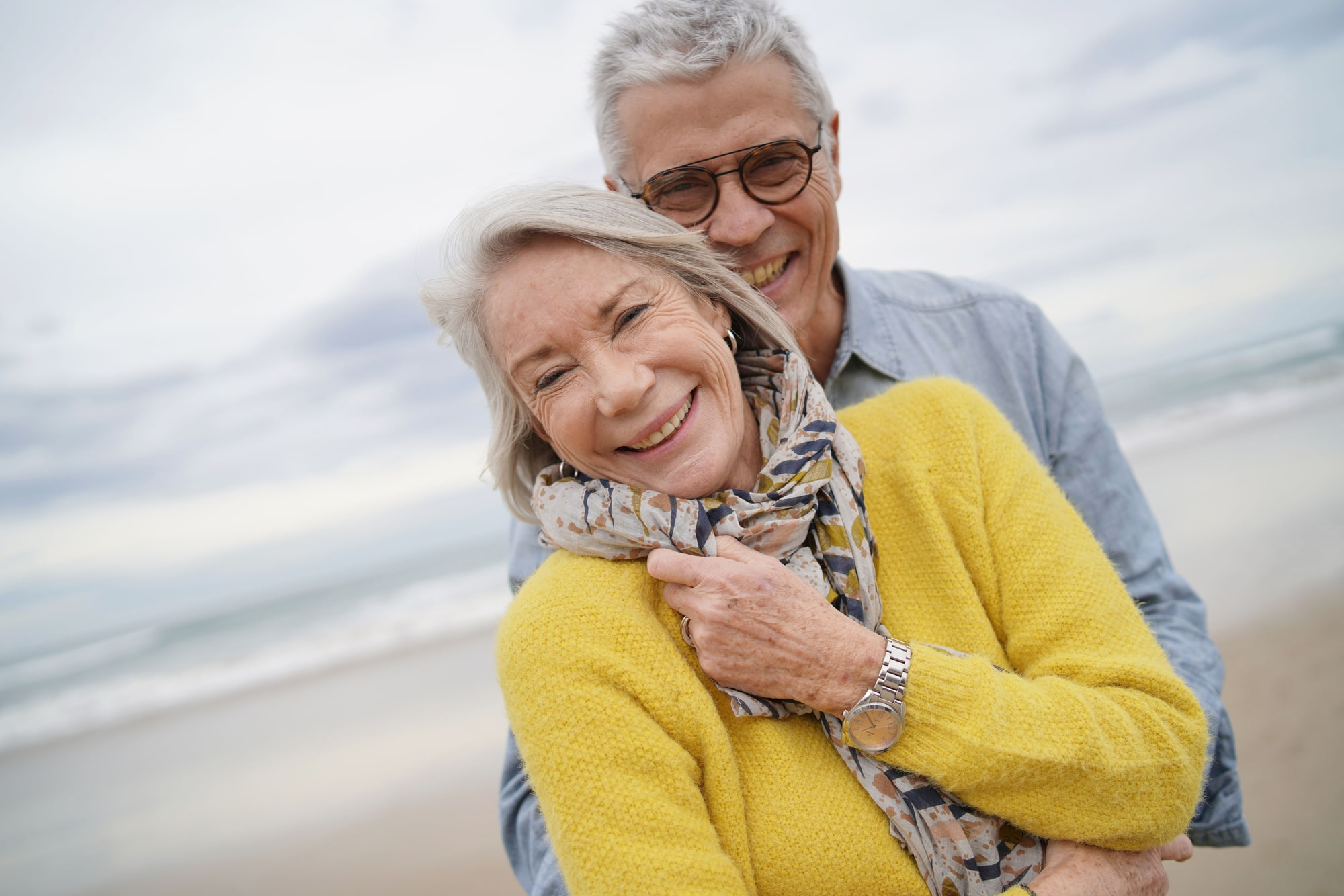 Portrait of attractive vibrant senior couple embracing on beach in fall