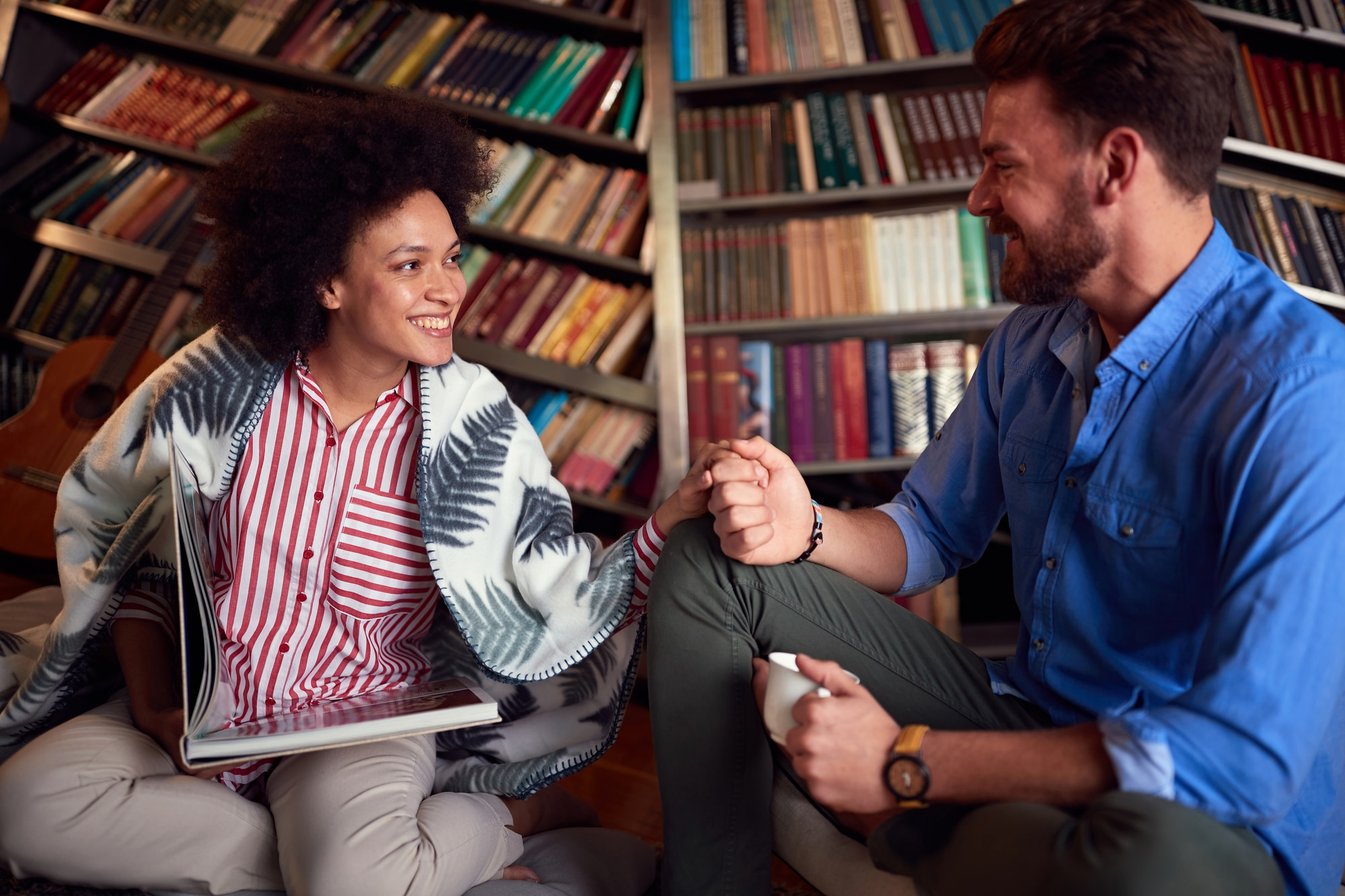 Romantic smiling man and woman enjoying at home reading a book.