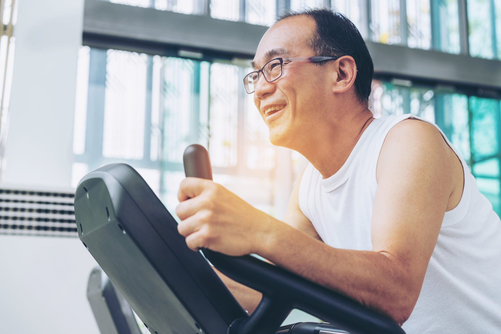 Senior man exercise on treadmill in fitness center. Mature healthy lifestyle.