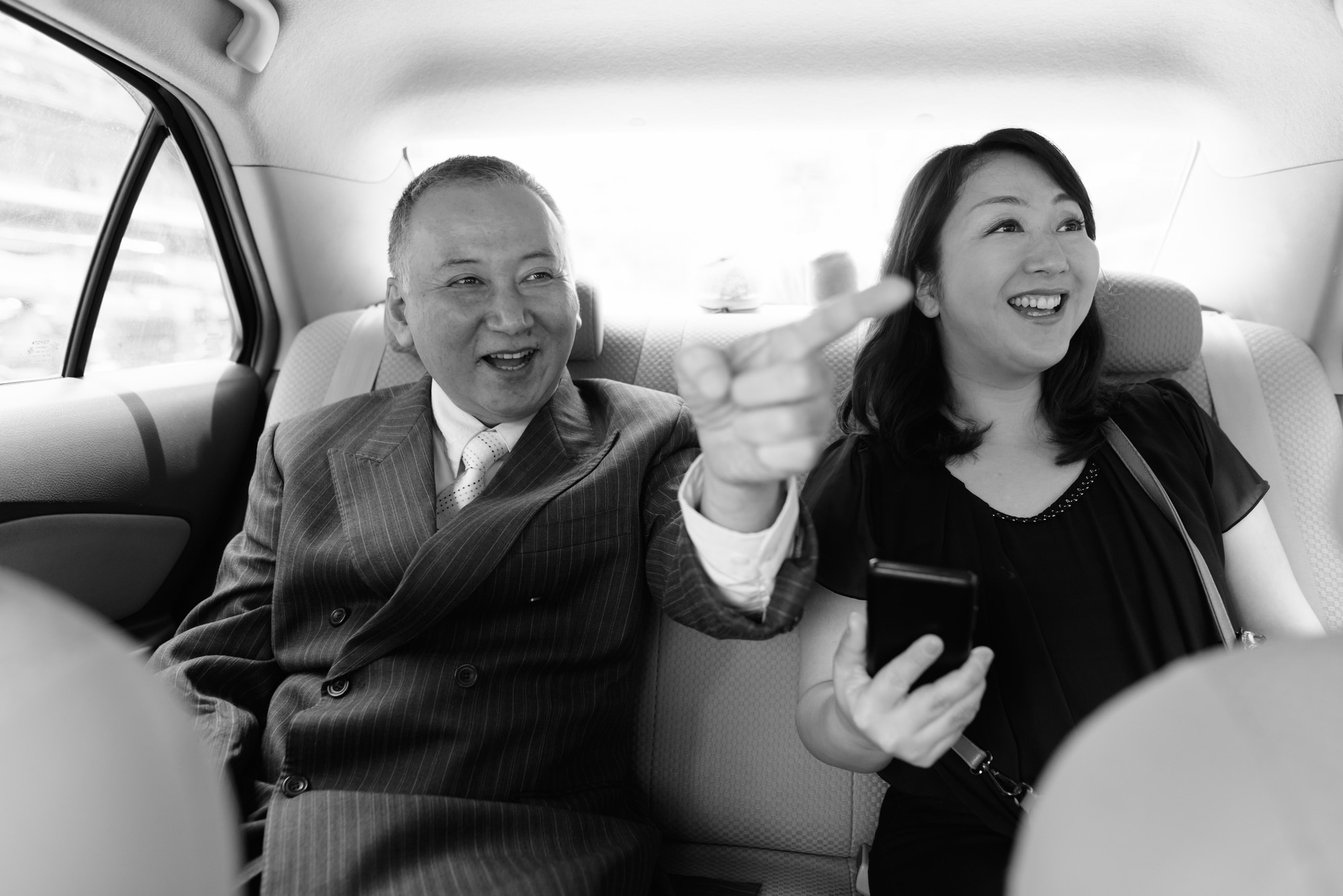 Portrait of mature Asian businessman and mature Asian woman exploring the city of Bangkok in black and white