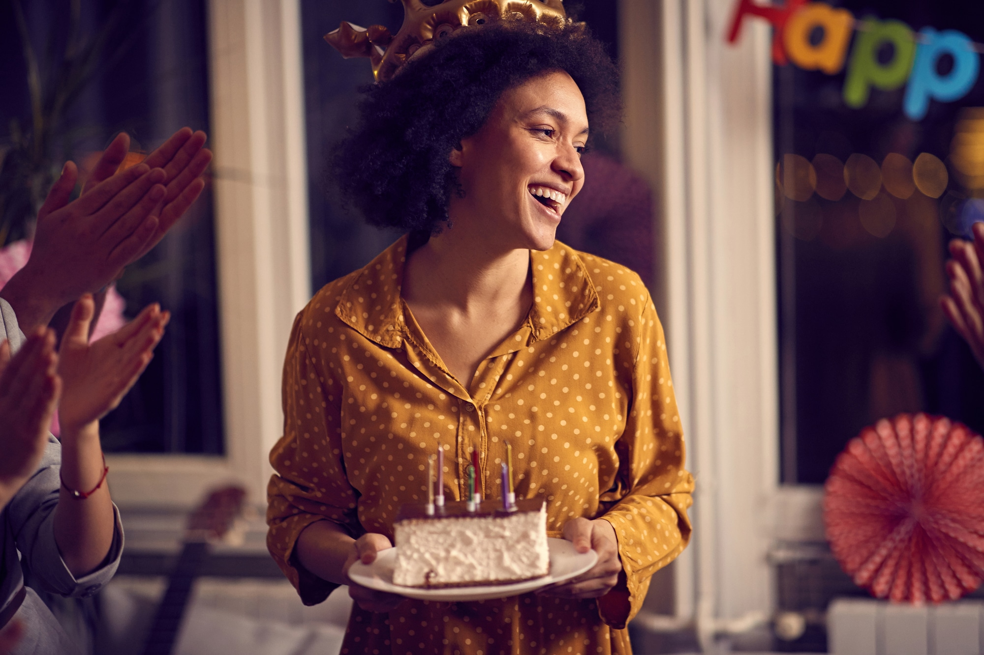 Happy young woman holding birthday cake and celebrating Birthday