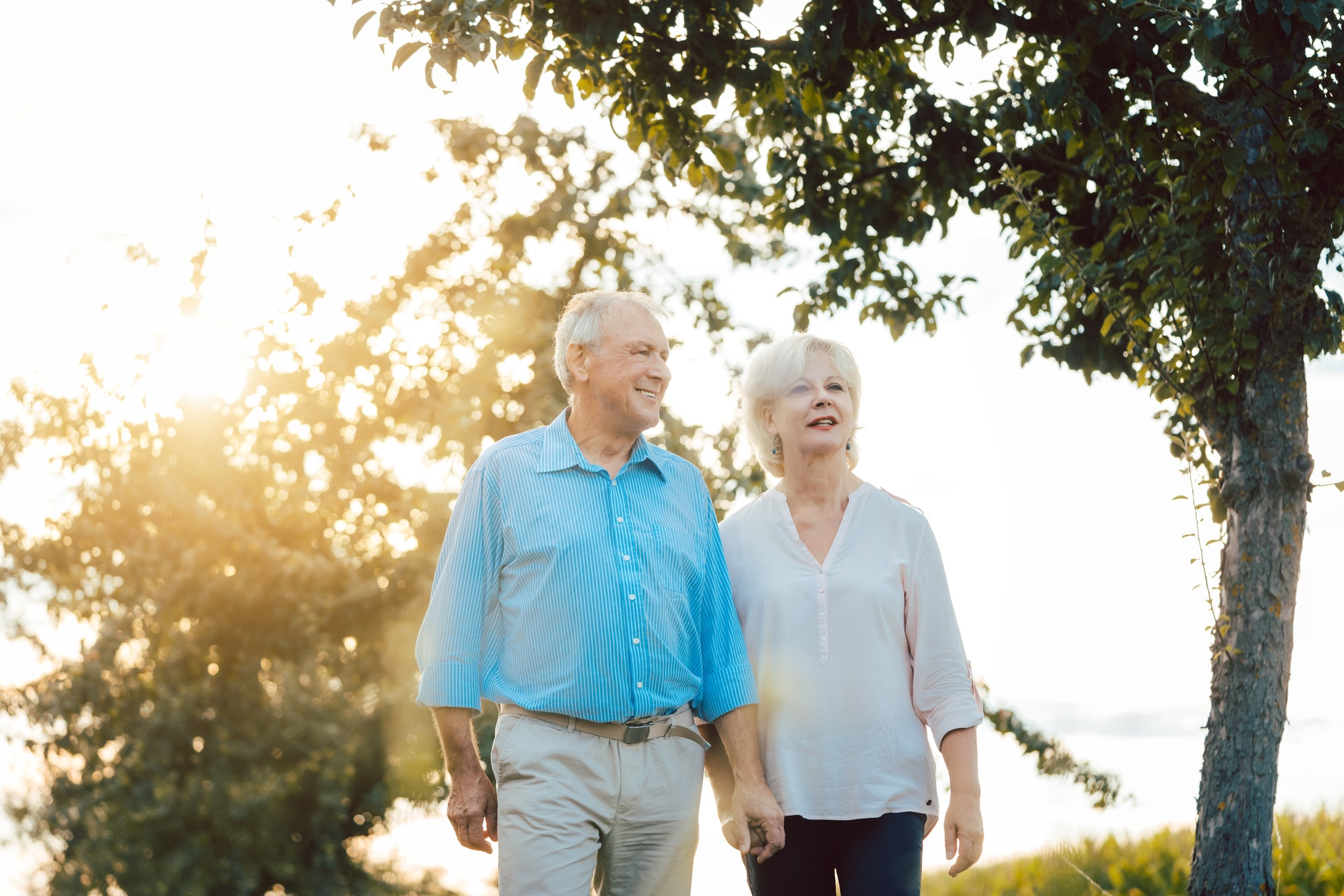 Senior woman and man having a walk along path on an evening in the countryside