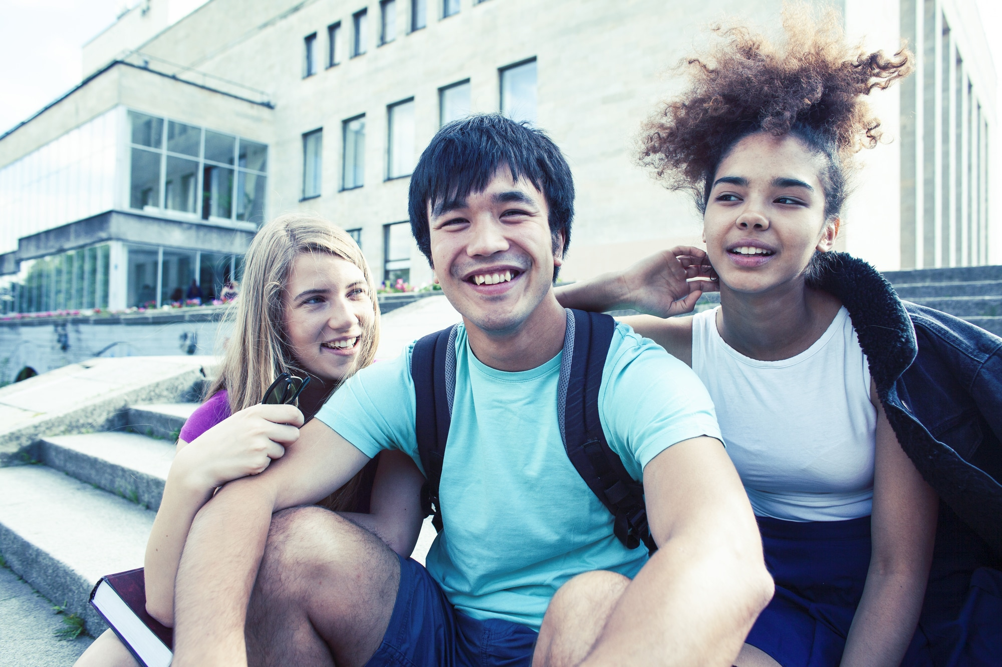 cute group of teenages at the building of university with books huggings, diversity nations real students lifestyle closeup
